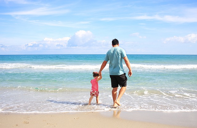 father holding hands with daughter walking in shallow water at beach