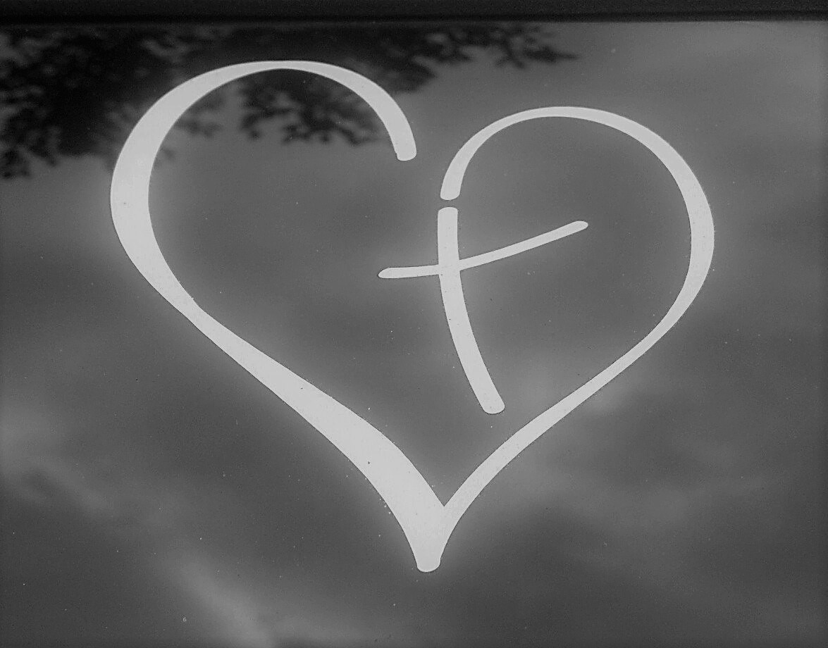 outline of white heart, with cross in centre, on black and white background